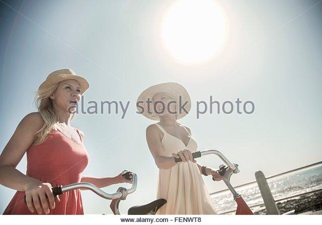 Junge Frauen, die zu Fuß mit dem Fahrrad am Meer Stockbild