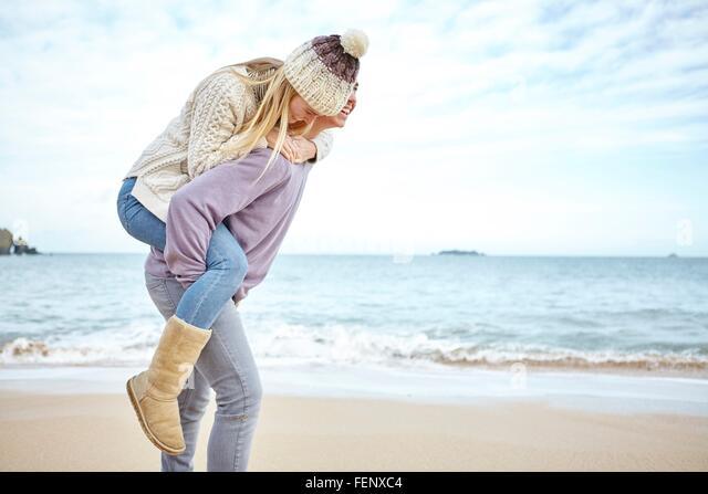Junger Mann mit Freundin eine Huckepack auf Strand, Konstantin Bay, Cornwall, UK Stockbild