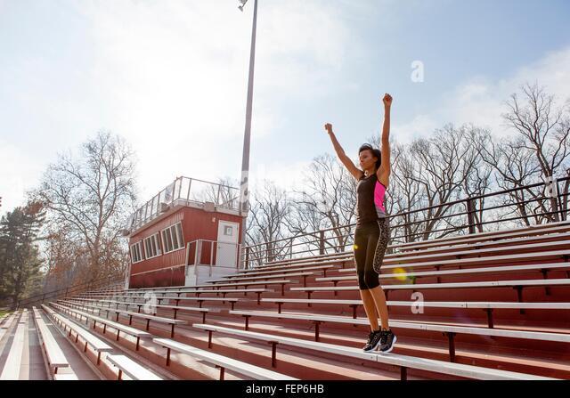 Junge Frau trägt Sportbekleidung, Arme heben, feiern Stockbild