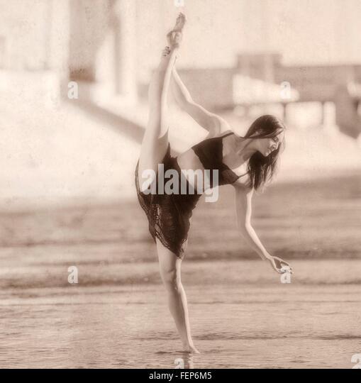 Junge Frau Bein angehoben, balancieren auf einem Bein, b&w, Los Angeles, Kalifornien, USA Stockbild