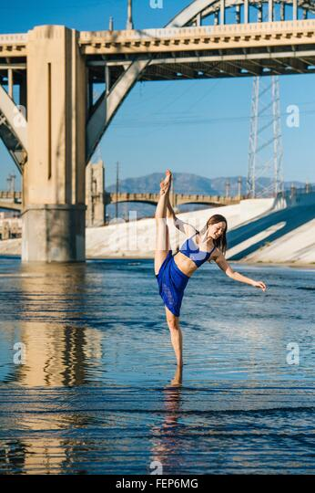 Tänzerin Knöchel tief im Wasser, Bein angehoben, balancieren auf einem Bein vor Brücke, Los Angeles, Stockbild