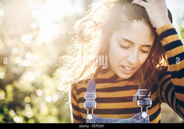 Junge Frau in ländlicher Umgebung, mit Fingern durch das Haar Stockbild