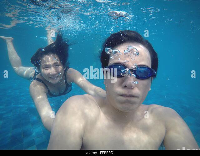 Mann mit lächelnden Frau Schwimmen im Pool Stockbild