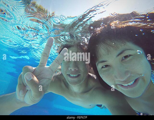 Lächelnd Mann mit Frau, Peace-Zeichen beim Schwimmen im Pool Stockbild