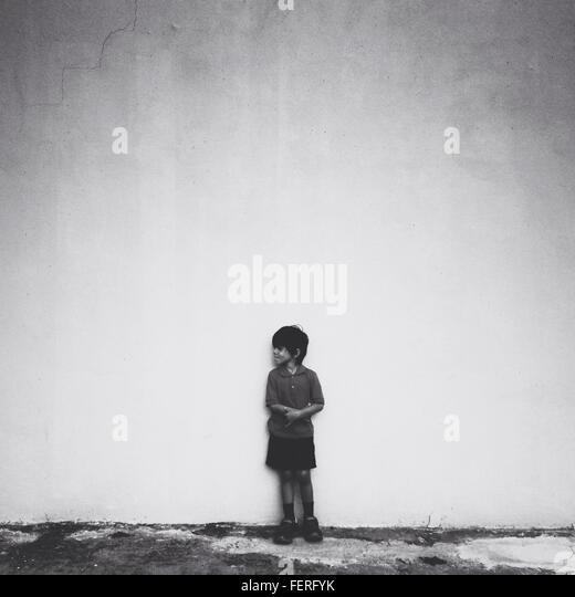 Gesamte Länge der junge Stand gegen die Wand während wegschauen Stockbild