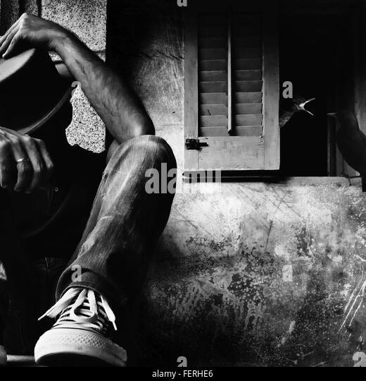Mann mit Hut, verlassene Wand sitzen Stockbild