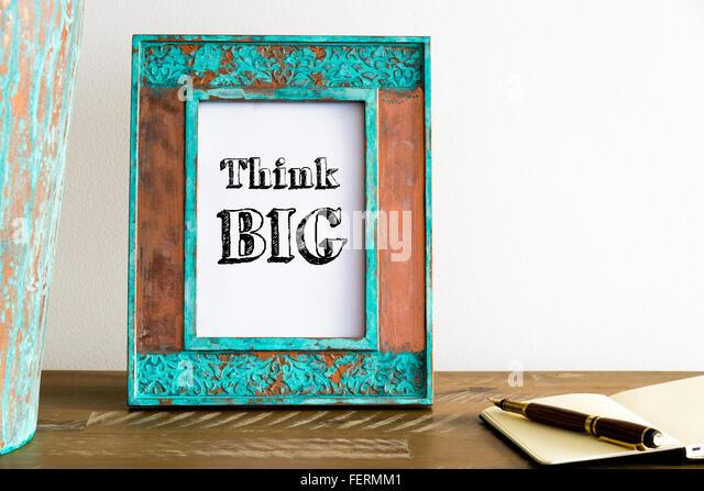 Vintage Bilderrahmen auf Holztisch über weiße Wand Hintergrund mit motivierenden Botschaft THINK BIG, Stockbild