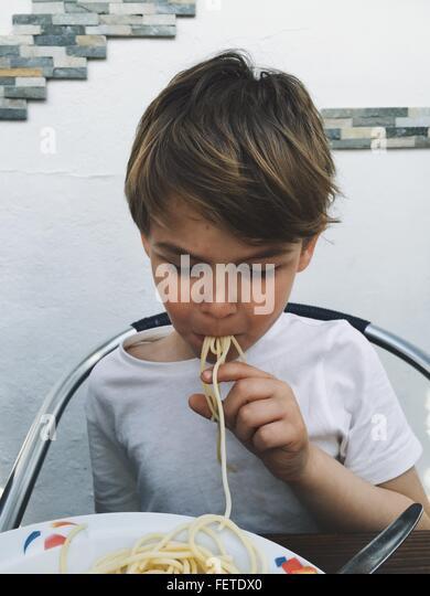 Junge essen Spaghetti zu Hause Stockbild