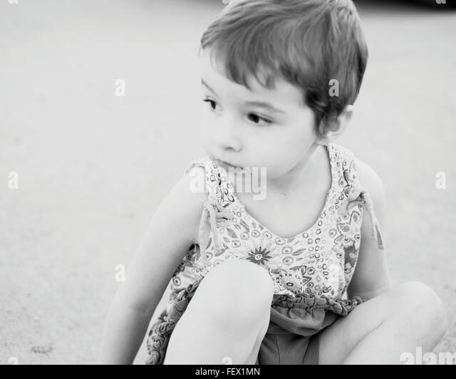 Niedliche Mädchen sitzen auf der Straße Stockbild