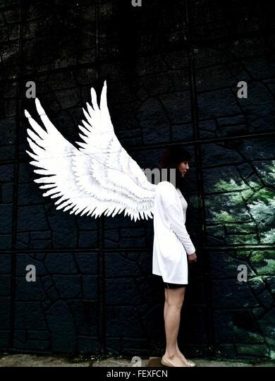 Frau stehend gegen Gemälde an der Wand Stockbild