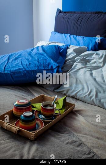 Ein paar Frühstück Tassen auf schmutzige Bettwäsche, die Hauptfarbe ist blau. Stockbild
