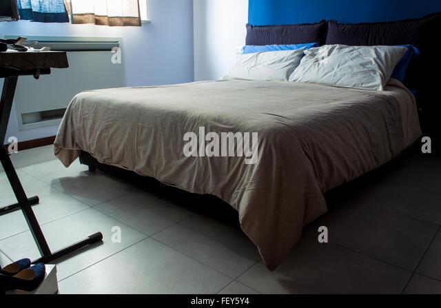 Ein kleines Schlafzimmer, helle Bettwäsche, die Hauptfarbe ist blau. Stockbild