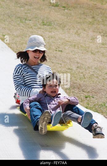 Mutter mit Sohn auf Folie im Park genießen Stockbild