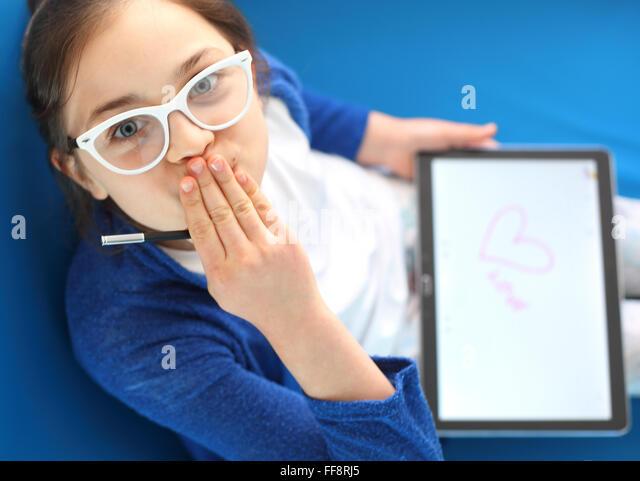 Erste Liebe, Mädchen zieht ein Herz. Ich liebe dich... Kind spielt mit tablet Stockbild