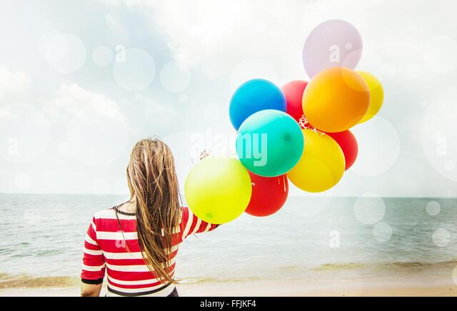 Frau mit bunten Luftballons am Strand, im freien Lebensstil filtert Bild Stockbild