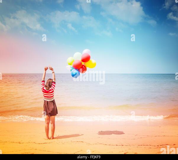 Frau mit bunten Luftballons am Strand, im freien Lebensstil Filter Bilder Stockbild
