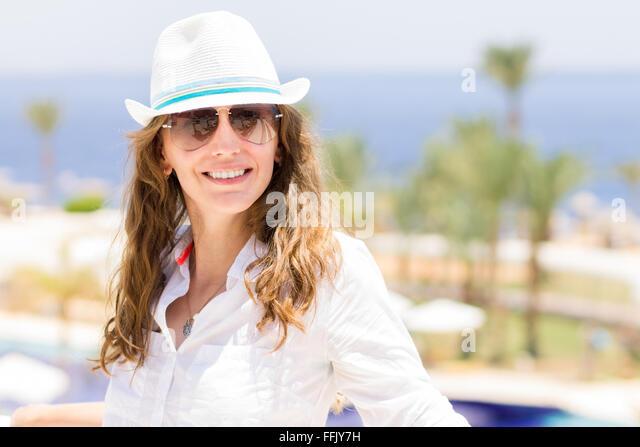 Junge europäische lächelnde Frau in weißem Hemd und Hut im tropischen Resort. Sommer Urlaub Hintergrund Stockbild