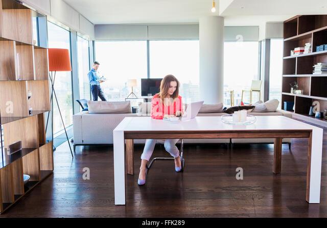 Frau in der Wohnung mit Laptop mit Mann im Hintergrund Stockbild