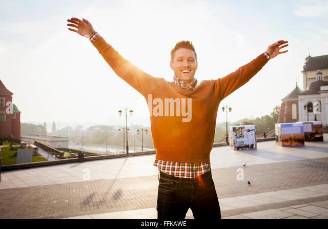 Mitte erwachsener Mann auf einer Städtereise mit erhobenen Armen stehend Stockbild