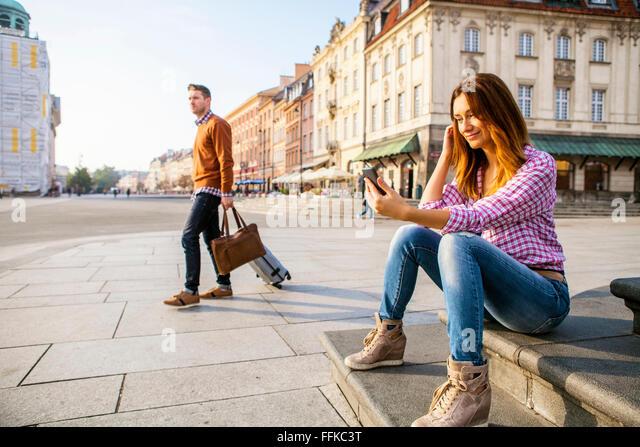 Mitte Erwachsene Frau mit Smartphone mit Mann im Hintergrund Stockbild