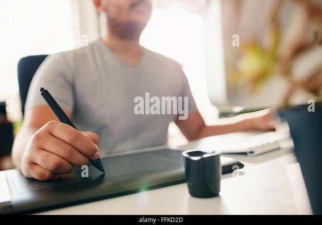 Hand des männlichen Designer arbeiten an seinem Schreibtisch mit Stift und digitaler Grafiktablett. Stockbild
