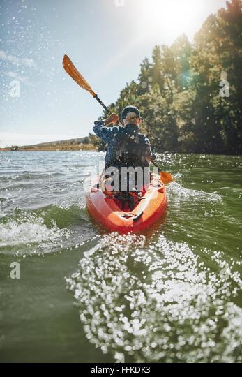 Rear View-Bild eines reifen Mannes, an einem sonnigen Tag in einem See paddeln. Senior woman eine Kajak zu paddeln. Stockbild
