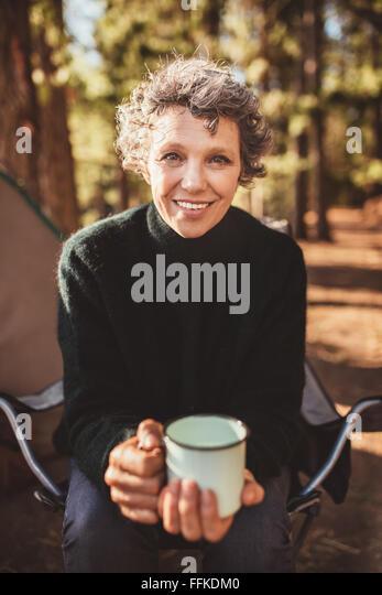 Porträt von senior Frau sitzt vor dem Zelt mit einer Tasse Kaffee. Kaukasische Frau hält eine Kaffeetasse, Stockbild