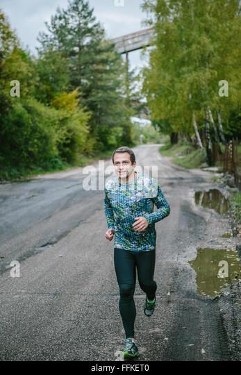 Mann läuft auf eine alte Straße in der grünen Natur. Stockbild