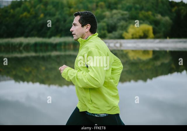 Mann in gelb Neon Jacke Runnig am See Stockbild