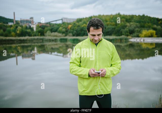 Läufer am See mit Smartphone Musik hören Stockbild