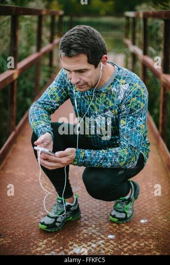 Läufer auf rostigen Brücke mit Smartphone Musik hören Stockbild