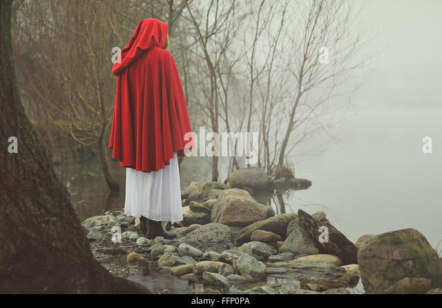Kleine rote Reiten Haube an einem Ufer eines nebligen Sees. Traurigkeit und surreale Konzept Stockbild