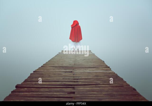 Rot mit Kapuze Frau schaut an nebligen See auf einem hölzernen Pier. Trauer und Einsamkeit-Konzept Stockbild