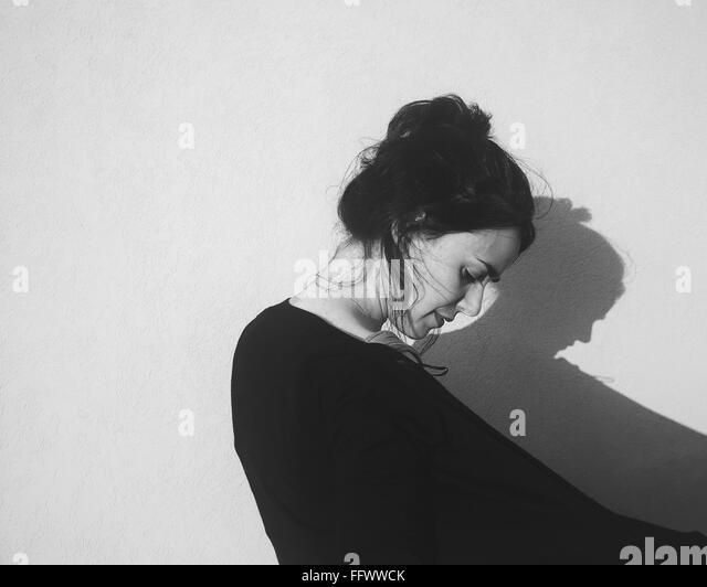 Frau, die gegen die Wand zu Hause Stockbild