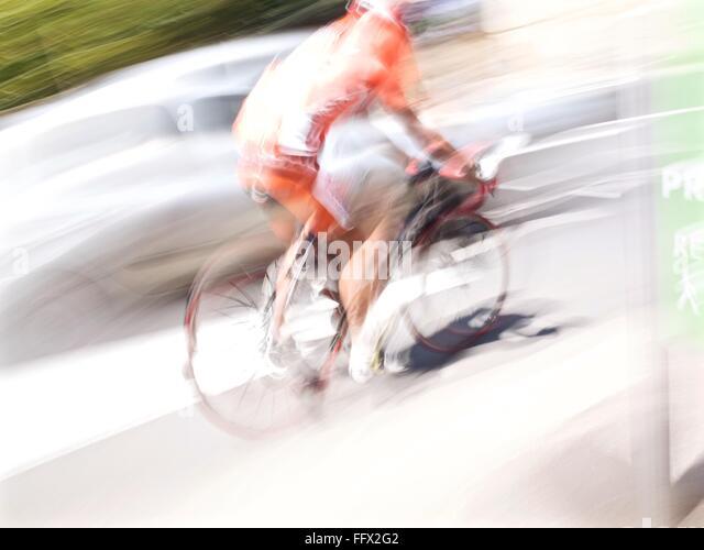 Bewegungsunschärfe von Mann mit Fahrrad unterwegs an sonnigen Tag Stockbild