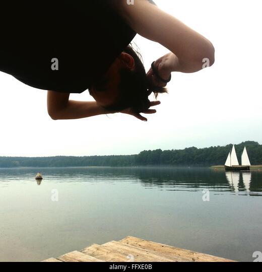 Niedrigen Winkel Ansicht von Frau binden Haare am Pier am See gegen Himmel Stockbild