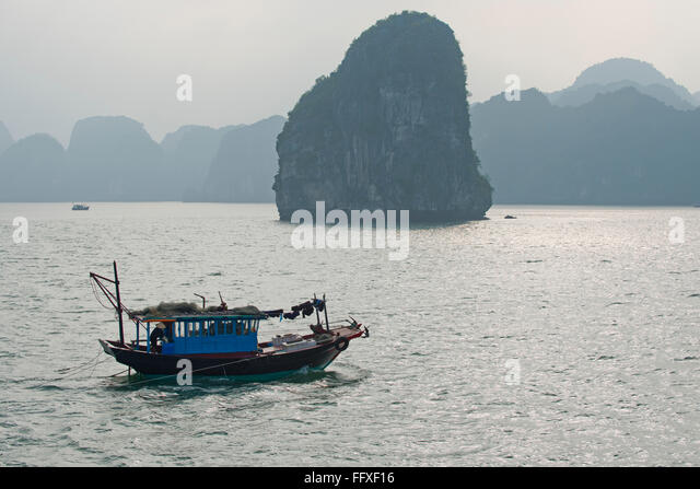 Ein kleines Fischerboot, Autofahren in ruhiger See in der Halong Bucht mit nebligen Kalkstein Karst hinter Vietnam Stockbild