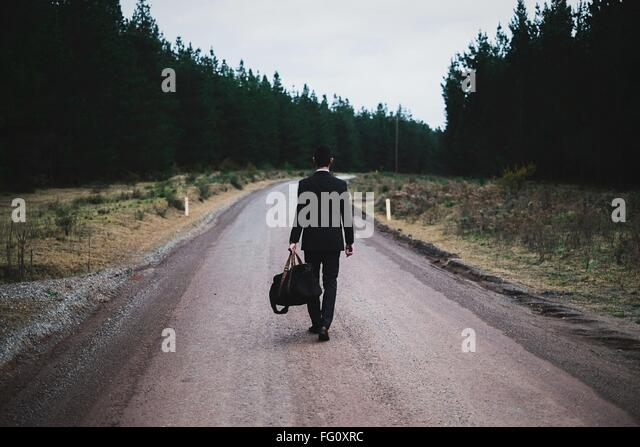 Voller Länge Rückansicht des Menschen mit Gepäck zu Fuß auf die Straße gegen Himmel Stockbild