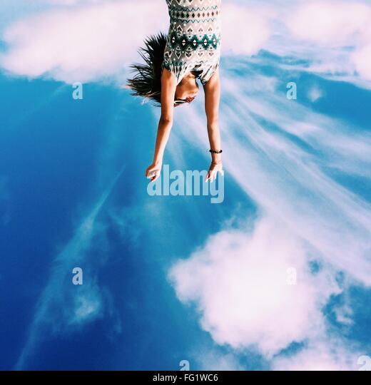 Bild der jungen Frau mit gegen Himmel erhobenen Armen auf den Kopf Stockbild