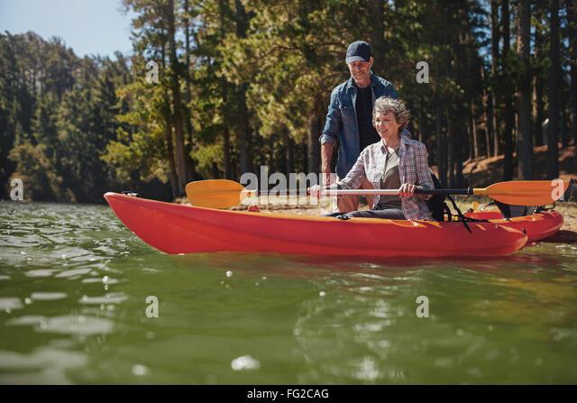 Porträt des reifen Mannes Unterweisung Frau eine Kajak im See paddeln. Ältere Frau bekommen Kajak Lektionen Stockbild