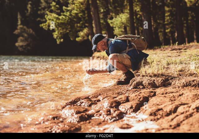 Porträt von reifer Mann sein Gesicht mit Wasser waschen. Senior kaukasischen Mann waschen Gesicht vom Wasser Stockbild