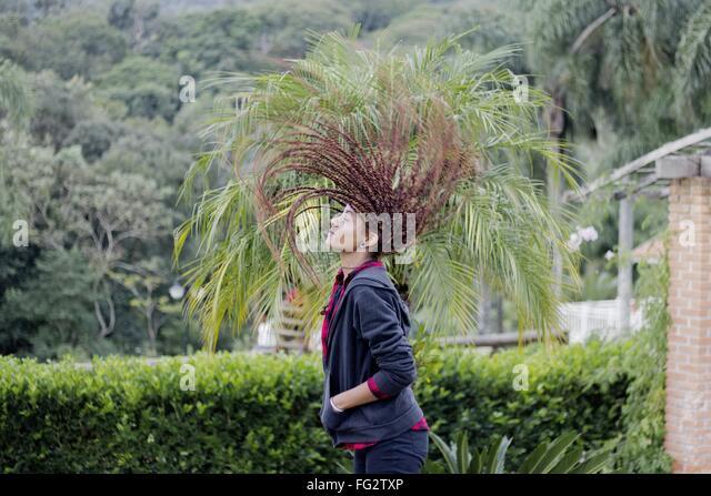 Frau mit zerzausten Haaren gegen Bäume Stockbild