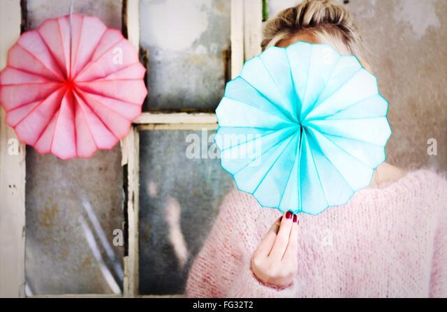 Frau mit blauem Bütten Fan vor Gesicht Stockbild