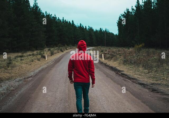 Rückansicht der Mann zu Fuß auf Landstraße Stockbild