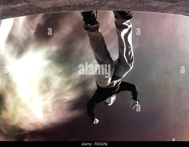 Bild des Menschen, die auf Felsen gegen Himmel auf den Kopf Stockbild