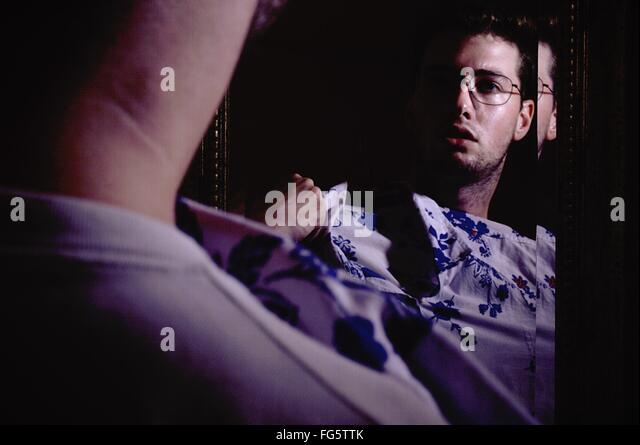 Reflexion der Mann versucht Shirt im Spiegel Stockbild