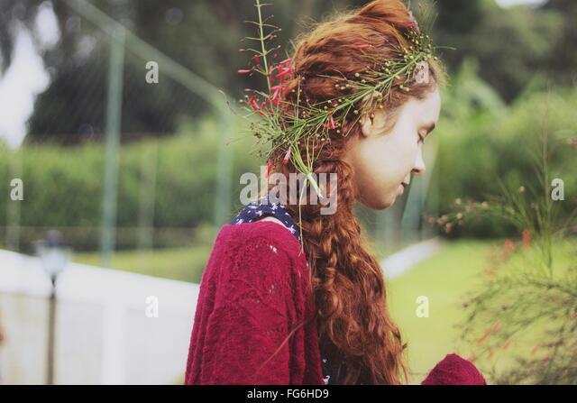 Seitenansicht der jungen Frau mit Blumen im Haar Stockbild