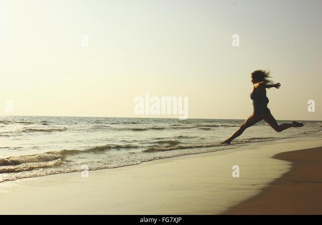 Semi-gekleidete Frau läuft in Richtung Meer am Strand gegen klaren Himmel Stockbild