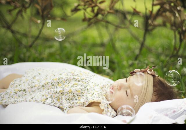 Babymädchen umgeben von Luftblasen im Park Stockbild