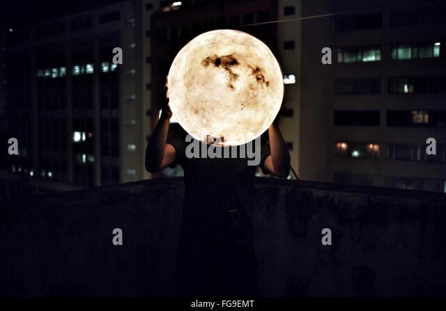 Mann, der künstliche Mond in der Nacht Stockbild